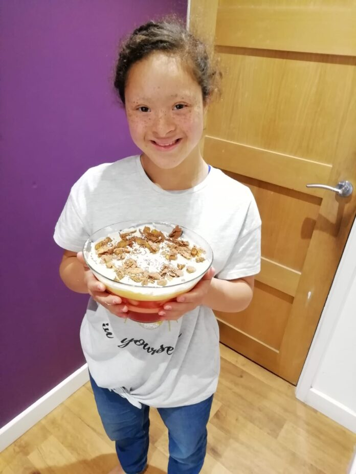 Ruby, wearing a white shirt and holding a cake while smiling happily at the camera