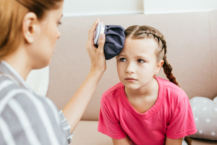 child with dyspraxia who got hurt being comforted by her mother