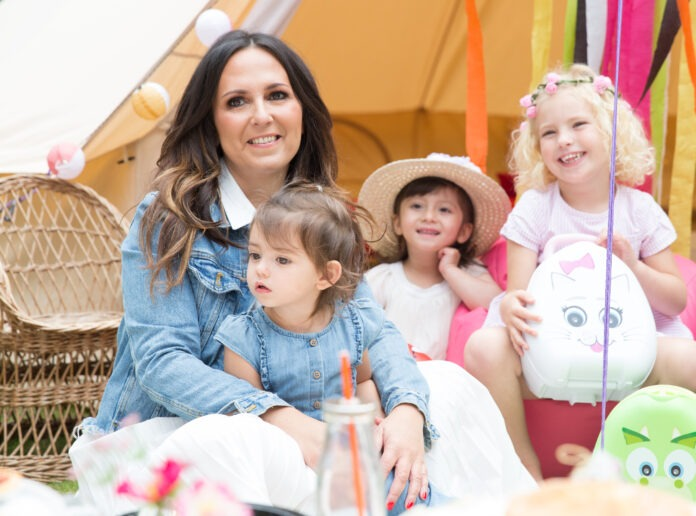 Potty Training teacher Amanda Jenner sits on a floor, with three small children around her.