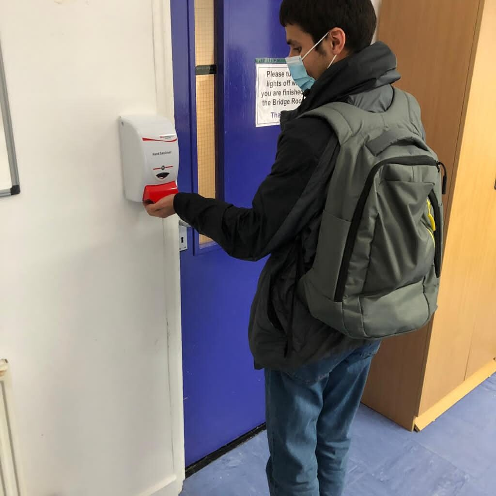 A teenager wearing a facemask and a backpack holds his hand under a hand sanitizing machine
