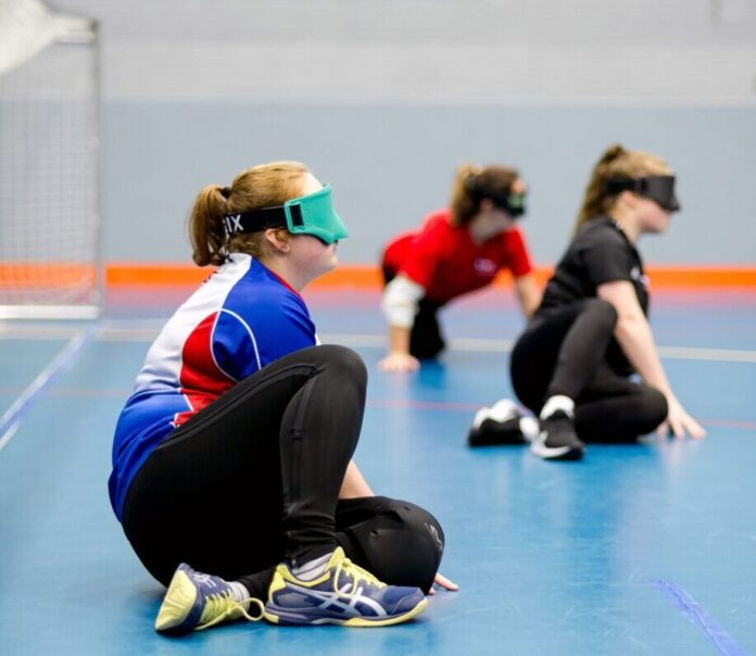three teenagers sit in a sports hall with their eyes covered