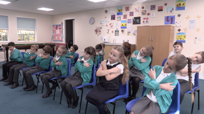 A class of children, all crossing their arms, doing an exercise that promotes good attachment