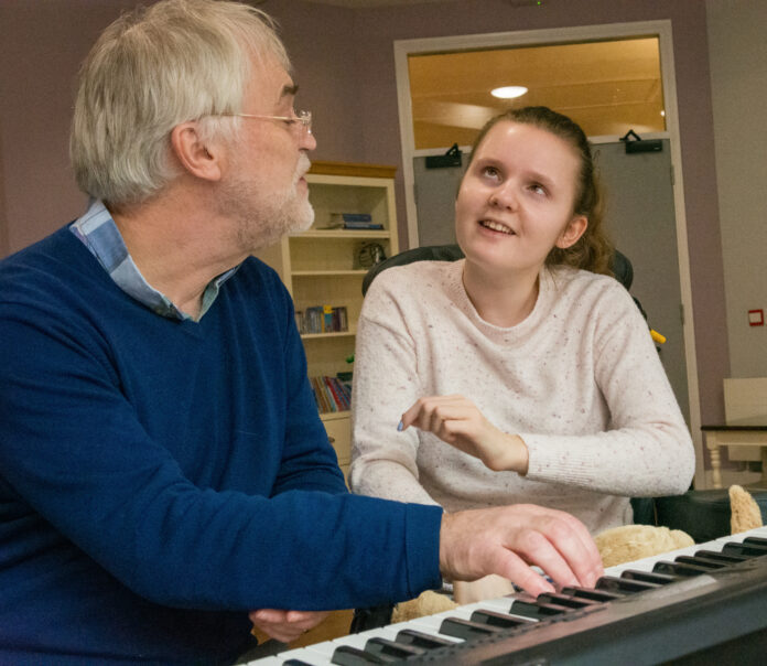 Dr Adam Ockleford, a man with gray hair and a blue jumper, plays the piano for Lily, who has juvenile dementia and is wearing a pink jumper