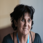 A photo of Catherine Brennan. She has short black hair and is wearing a blue lanyard and black shirt