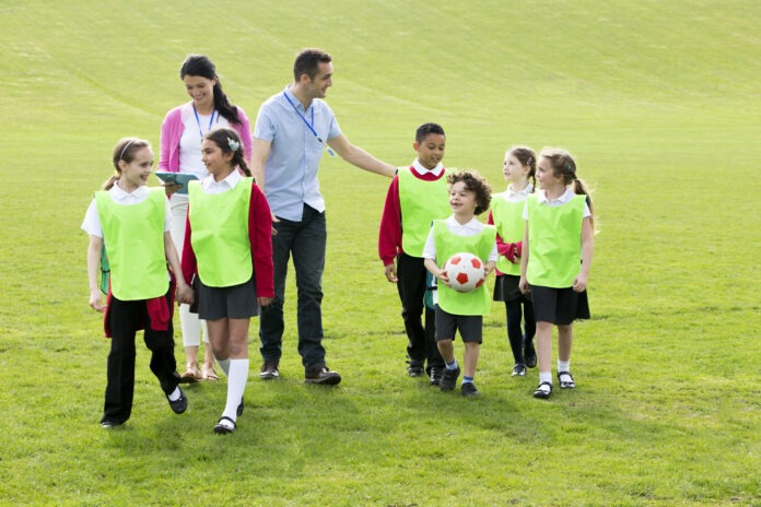 Group of school children wearing bibs and school uniform outside on the grass with their teacher. One of the boys is holding a soccor ball.